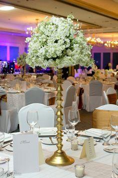 Centro de Mesa de Doble altura pero de base delgada ideal para salones grandes ya que hace lucir el salón más decorado, y al mismo tiempo en la mesa no evita que los invitados admiren cada momento de la boda., desde Feztiva.com