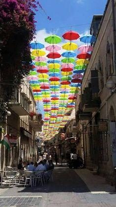 Umbrellas over a side street in Jerusalem.