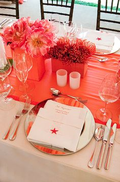 Each metallic plate is topped with a white hemstitched napkin and a small orange starfish.
