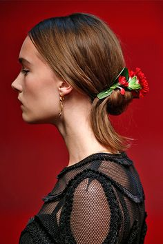 Flower Child By now, we all know the story of Dolce & Gabbana's Sicilian fantasy woman. But, this vintage-inspired lady was bestowed with a renewed interest this season thanks to Guido Palau, who adorned her typical braided chignon with blood-red roses, which almost matched her lipstick.