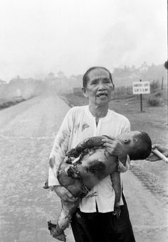 "June 8, 1972.  Huynh Cong ""Nick"" Ut. A Vietnamese grandmother carries her severely burned one-year-old grandson down Route 1 after a misdirected napalm attack by South Vietnamese pilots in the village of Trang Bang, South Vietnam."