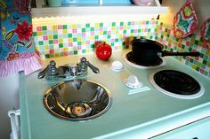 """LOVE this play kitchen! Love using the sink strainer to make it look like a real drain. Love the backsplash. I think I might also add a chalkboard area on one side, or maybe a magnet board on a """"refrigerator"""" section? SO many ideas. Diy Play Kitchen, Play Kitchens, Kitchen Ideas, Stove Drip Pans, Easy Diy Projects, Craft Projects, Easy Peasy, Play Houses, Home Crafts"""
