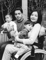 Photo: A mother sits in a wheelchair  smiling, with a small boy facing her, in her lap.  On her right side is  her husband sitting in a chair.  His left arm is over her wheelchair.   In his right arm he is holding a baby in a sort of standing position.