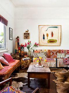 Décoration bohême dans ce salon qui accumule les couleurs et les motifs, avec ses peaux de bête au sol.