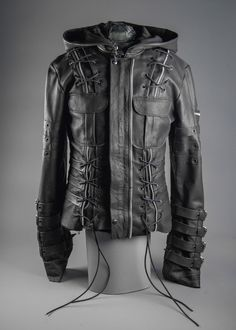 The Junker Designs Chainsaw Jacket features heavy duty leather and zippers, handmade straps, plenty of hardware and an over-sized removable cloak hood. The right upper arm has a black