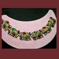 "This beautiful gold tone bracelet by TRIFARI features lush emerald green, ruby red and sapphire blue cabochons sprinkled with tiny faux diamonds and is set in a detailed gold tone swirl design. It measures 7"" in length, 3/4"" in width and comes in excellent condition. Always a name synonomous with ""quality"" this TRIFARI bracelet is true to that legacy.  SOLD"