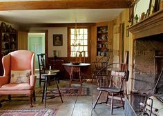 A collection of early American furniture adds to the ambience of what was once the all-purpose main room. Note the cooking fireplace and wide-board floors.