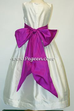 Flower girl dresses with a purple or green bow.