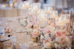 yummy wedding table centerpiece. Love the mixture of tall cylinder vases with floating candles with the lush flowers and the tiny bits of babies breath makes it sooooo girly!!