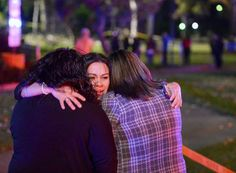 People close to the wedding party embrace as Los Angeles County Fire Dept. firefighters work at the scene where a large tree fell on a wedding party in Whittier, Calif., Saturday, Dec. 17, 2016.