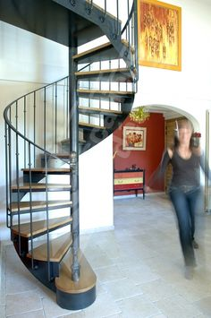 Photo DH45 - SPIR'DÉCO® Bistrot sans contremarche. Escalier intérieurhélicoïdal métal et bois pour une décoration rétro. Cet escalier en fer forgé, avec son look 'fin XIXème siècle', sa rampe ornée, la chaleur de ses marches bois, s'intègre dans tout type d'intérieur avec charme et caractère. Limon formant crémaillère en tôle roulée. Option 1ère marche arrondie et débordante formant podium de départ + poteau décoratif en fonte moulurée avec boule acier en tête. Finition : Acier brut patiné.