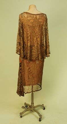 BEADED GOLD METALLIC LACE DRESS with FAN MOTIF, c. 1920. Sleeveless with attached capelet, the lace in a ginko leaf pattern, a band of bugle bead fans in rose, cobalt, gold and silver circles the draped waist and adorns a flounce on left side, seams and edges trimmed with a band of gold beading, sand lining with lame straps. Back