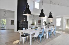 Zwarte hanglampen boven een eetkamertafel, metalen stoelen, lange tafel en stalen kast. #interieur #hanglamp #hanglampen #interior #pendant #pendantlight