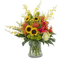 Harvest Wisp Bright orange Lilies and Pin Cushion Protea, mixed with lovely yellow Sunflowers make a bold statement.