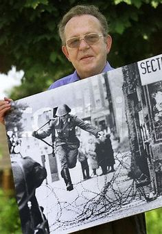 German photographer Peter Leibing displays his famous picture of the East German soldier Conrad Schumann jumping over the Berlin Wall. Leibing's photograph of the 19-year-old East German border guard throwing away his rifle as he hurled over barbed wire on his way into West Berlin was taken on August 15, 1961, two days after East Germany sealed off its border with the wall. (http://www.videofact.com/cold_war/berlin/berlin43e_2.htm)