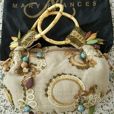 """NWOT Mary Frances Purse Dare to be stunning with this Mary Frances purse.  Still stuffed with the original paper, the artistry & craftsmanship of this canvas beaded beauty includes blue rosebuds, yellow toggles and more.  It measures 10"""" wide by 6"""" high.  As you can see from shopping in my store, I have been a long time collector of handbags.  Most of the bags you see in my shop have always been displayed in a glass case in my home, including this Mary Frances.  A rare jewel. Mary Frances…"""