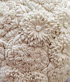 Merging botanical forms from England with the delicate plant shapes from her childhood in Japan, ceramic artist Hitomi Hosono produces delicate layered sculptures that appear as frozen floral arrangements. Often monochromatic, the works are focused on carved detail rather than color