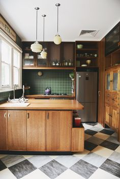 Kitchen with wood cabinets, green tile backsplash, and black and white tile floor