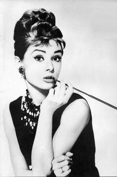 "Audrey Hepburn as Holly Golightly with her cigarette holder while wearing a long black gown. Two best known movies were  ""My Fair Lady"" and ""Breakfast at Tiffany's""."