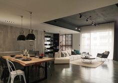 Public spaces are open yet well defined. A raised ceiling in matte charcoal helps to delineate the open living room space. The dining and kitchen, on the other hand, enjoys the rustic treatment of playfully misaligned wood panels.