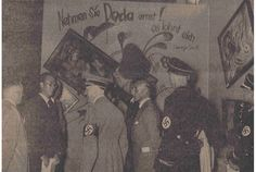 "Adolf Hitler and other Nazi officials standing by the Dada wall at the ""Entartete Kunst"" (Degenerate Art) exhibition, July 16, 1937. Paintings by  Kandinsky, Klee, and Schwitters have been deliberately hung askew and are accompanied by a slogan penned by George Grosz. This photo was published in the Nationalist Observer, South German (Süddeutsche) issue, No. 199, July 18, 1937. Staatsbibliothek zu Berlin Stiftung Preussischer Kulturbesitz"