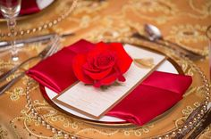 Red roses on each plate at the reception is an elegant and beautiful touch
