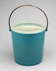 SECCHIO TONDO CON COPERCHIO (1954) di Gino Colombini. Emerge per l'originalità dei particolari quali: il raccordo tra plastica e ferro, la sensibilità funzionale della presa del coperchio, l'essenzialità e robustezza delle sezioni. Il coperchio con la sua forma incavata funge da vassoio di contenimento per sapone, spazzola o straccio. Con questo prodotto la Kartell vince nel 1955 il suo primo Compasso d'oro.