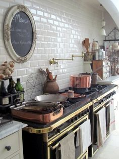 French style kitchen - black and brass ovens, copper pots, brass pot filler faucet, classic white subway tiles