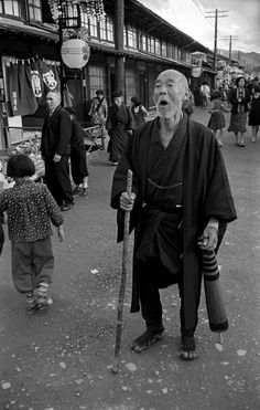 Old Japanese man in kimono with cane.