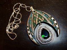 Hand tooled leather iridescent pendant with emerald green rhinestone in sterling…