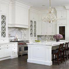 Elegant, glamorous kitchen with white cabinetry and X-front glass doors. Grand kitchen island with farmhouse sink. Carrara marble countertops with herringbone accent tiles behind cooktop with pot filler. Tiled floor, gold and crystal chandelier and mahogany barstools. Glass-front wine cooler and polished nickel bridge faucets. @ DIY Home Design