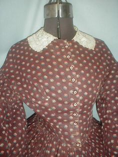 "1860s cotton print dress, terra cotta, white & teal blue on brown background; bodice lined in cotton & has front button closure, piping at neck, armscyes & waist; skirt unlined, cartridge pleated, light underarm discoloration; embroidered collar original to dress; bust: 34""; waist: 28""; skirt length: 41""; hem width: 180"": ebay seller fiddybee"