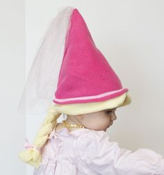 Princess style cap has beautiful decorative trim, a tulle train and built-in blonde hair, complete with a thick braid tied with a pink ribbon. Soft fleece makes it super comfortable, lightweight and easy to wash.