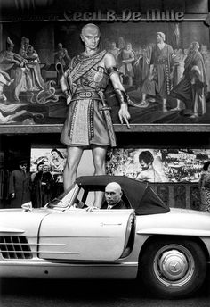 Yul Brynner in his Mercedes-Benz 300SL Roadster as he pulls up to the premiere of the 1956 Cecil B. DeMille blockbuster named The Ten Commandments.