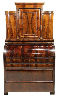 "Biedermeier cylinder top secretary, circa 1840, executed in flame mahogany in two parts, the top having a stepped cornice above a centered door opening to shelves, flanked by Corinthian columns and curved doors surmounting the desk, having a cylinder top opening to a fitted interior with ebonized trim, pulls, and columns, the retractable blaze covered writing surface above three graduated drawers, the whole rising on block feet, 51""h x 44""w x 24""d"