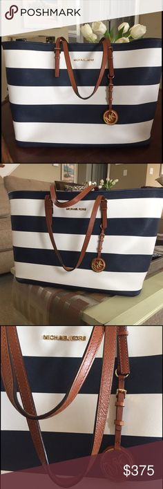 Michael Kors Jet Set Navy White Striped EW Tote Preppy, nautical and classic Michael Kors East West saffiano leather tote. Looks brand new; only carried a handful of times. Size Medium but this is a LARGE Tote suitable for a weekend bag or carry-on... JET SET indeed. One zip pocket inside, clip closure to hold the tote closed. Only selling for the right price... this is gorgeous, crisp, and SOLD OUT 😜 And I kind of want to keep it 🤗 Michael Kors Bags Totes