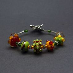 Handmade lampwork bracelet with handmade glass beads in red, green and yellow colors with crystal and metal beads, with ornate toggle-lock