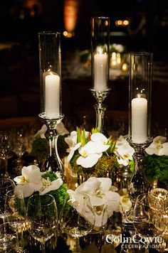 A trio of candles in varying heights illuminates a fresh table of orchids in greenery. Wedding Decorations, Centerpiece, Candle Holders