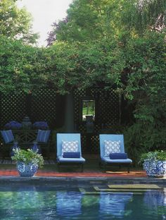 Dark green lattice, columns, blue and white porcelain and cushions by the pool - Carolyne Roehm