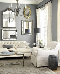 This tailored living room features a tufted sofa, collection of mirrors, and dark gray accents