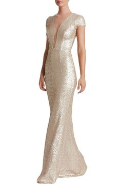 Dazzle through the evening in this slinky sequin gown that conceals and reveals with a plunging neck veiled by sheer mesh.