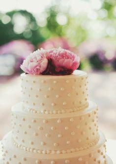 Bolo de casamento branco com bolinh) as imitando pérolas, decorado com flores (peônias) cor de rosa.