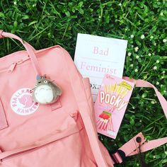 """a photo of a pink backpack, a book entitled """"bad feminist"""", and a box of pocky"""
