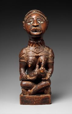 Figure: Seated Female Nursing Child  19th–early 20th century Geography: Democratic Republic of the Congo; Republic of the Congo; Angola Culture: Kongo peoples; Yombe group Medium: Wood, pigment, glass Dimensions: H. 21 1/2 in. (54.6 cm), W. 10 in. (25.4 cm), D. 9 1/2 in. (24.1 cm)