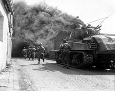#American soldiers supported by a M4 Sherman tank move through a smoke filled street in #Wernberg, #Germany, 1945. 11th Armored Division
