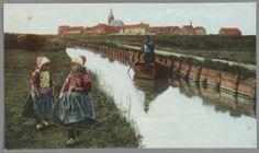 Op de voorgrond twee meisjes in klederdracht. Links een overnaadse ansjovisjol op het land. Man vaart in Marker binnenboot bomend langs de sschoeiing en het Zereidepad. Op achtergrond de Kerkbuurt. 1905-1915 #NoordHolland #Marken