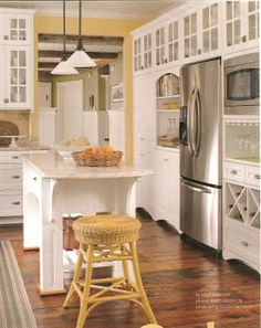 Kitchen with white cabinets, yellow walls, special built-ins