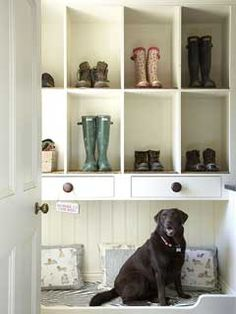 Just like a doormat, these mudroom cubby holes have carpet swatches inside to help remove dirt from work shoes. Plus, this space features a comfy spot for the family pooch to lounge. | Photo: Mark Scott
