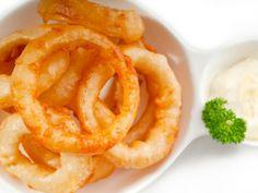 Острые луковые кольца:  лук репчатый крупный 3 шт. мука  1 стакан пиво  1 стакан красный молотый перец  0,5 ч. л. соль 0,5 ч. л.  растительное масло для фритюра  сухие хлопья перца чили