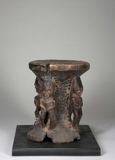 "People: Pende DR Congo H: 11"" The unusual stool with four caryatids, each carved differently, and the area between them decorated with hobnails. The stool seat emerging from the rough block."